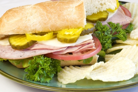 Italian submarine sandwich with chips on a plate closeup photo