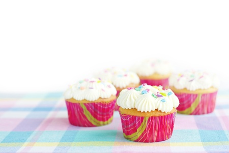 Delicious Easter cupcakes on a pastel spring colored placemat, horizontal with with copy space and selective focus