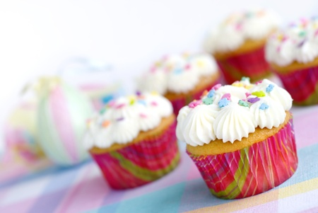 placemat: Vanilla Easter Cupcakes with sprinkles on a plaid pastel placemat with Easter eggs in the background, selective focus, copy space Stock Photo