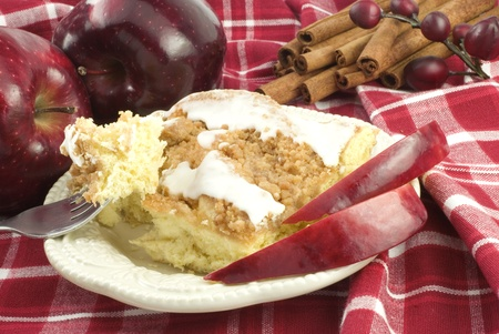 Sugar apple: A piece of apple cinnamon streusel coffee cake with white icing on a plate with a bite of cake on a fork, surrounded by apples and cinnamon sticks, copy space Stock Photo