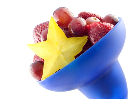 Colorful blue bowl of mixed fruit with starfruit, diagonal, isolated on white background with copy space