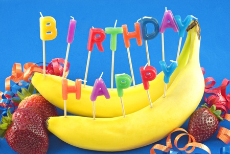 Candles spelling Happy Birthday stuck in bananas instead of cake for healthy lifestyle birthday, blue background with copy space Stock Photo
