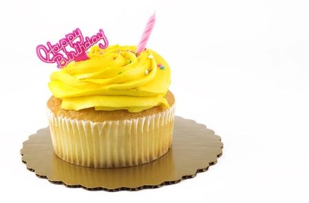 joyeux anniversaire: Un petit gâteau d'anniversaire jaune joyeux avec une bougie rose éteint et un message d'anniversaire, isolé sur blanc avec copie espace