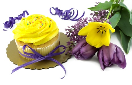 Yellow cupcake with purple ribbon beside bouquet of fresh purple and yellow tulips and lilac blooms, isolated on white with copy space Stock fotó