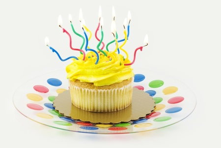 A yellow cupcake on a colorful plate with many colored lit candles isolated on gray background