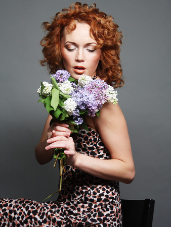 hand holding flower: Pretty redhair woman holding flowers