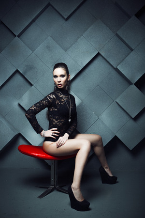 Portrait of a stunning fashionable model sitting in a red chair in modern style. photo