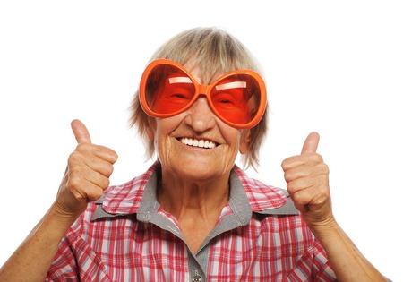 Senior vrouw met grote zonnebril doet funky actie geïsoleerd op witte achtergrond Stockfoto