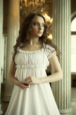 Portrait of a beautiful young victorian lady in white dress.