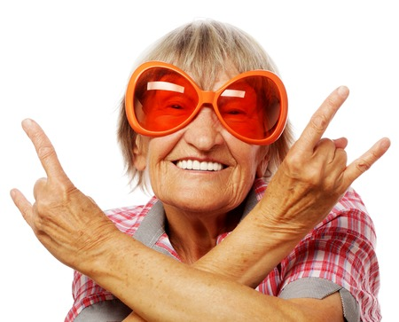 Senior woman wearing big sunglasses doing funky action isolated on white background 免版税图像