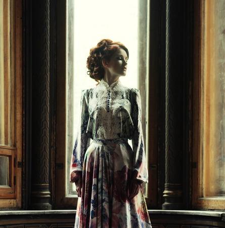 edwardian: young beautiful woman in pink dress posing in luxury palace