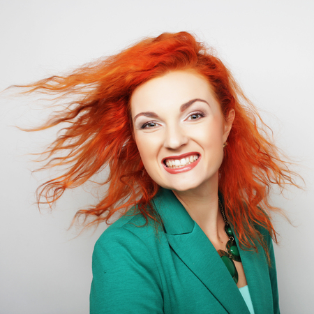 dishevel: Young happy red woman with wind in hair Stock Photo
