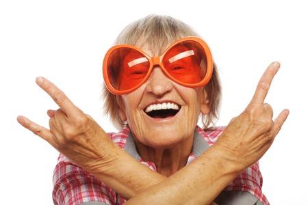 Hogere vrouw die grote zonnebril draagt ??die funky actie doet die op witte achtergrond wordt geïsoleerd Stockfoto