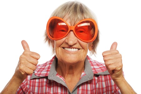 old hand: Senior woman wearing big sunglasses doing funky action isolated on white background Stock Photo