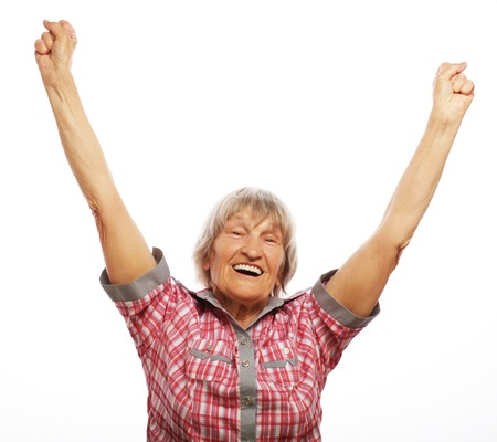 old people: portrait of a cheerful senior woman gesturing victory over a white background