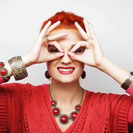 unfaithfulness: Pretty young woman looking for something with wide open eyes and imaginary binocular.rrr Stock Photo