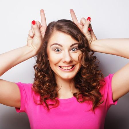 hand sign: Funny woman doing hand sign. Studio shot.