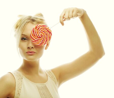 fashion blond woman  holding lollipop, posing against white  photo