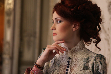 Mladá krásná žena stojící v palácové místnosti.