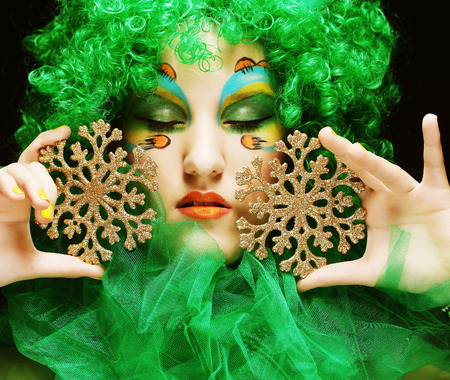 Beautiful lady with artistic make-up holding Christmas decorations.Doll style. photo