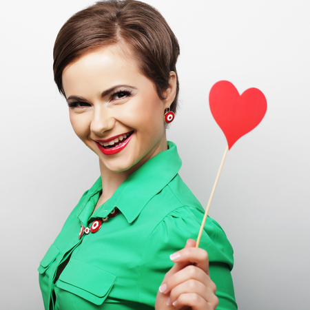 Young happy woman holding red  paper heart and ready for party photo