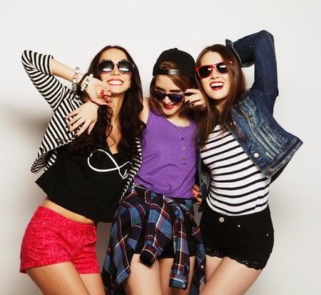 Drie stijlvolle sexy hipster meisjes beste friends.Standing samen en plezier maken. Kijken naar de camera. Over grijs.