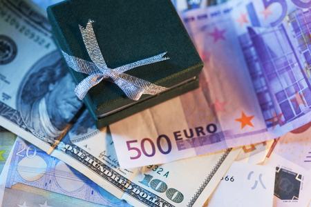 valorization: Present box and money - dollar and euro