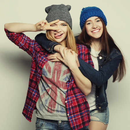 teens: two young girl friends standing together and having fun. Showing signs with hands. Looking at camera
