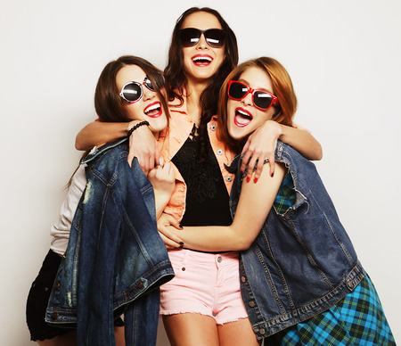 Fashion portrait of three stylish sexy hipster girls best friends, over gray background. Happy time for fun. Stock Photo