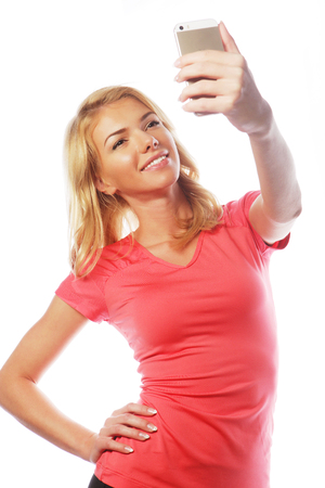 sporty blond woman making selfie, studio shot Stock Photo