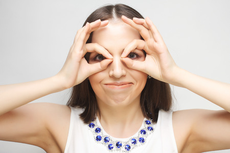 unfaithfulness: Pretty young woman looking for something with wide open eyes and imaginary binocular. Stock Photo