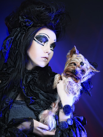 elegant dark queen with little dog over blue background photo