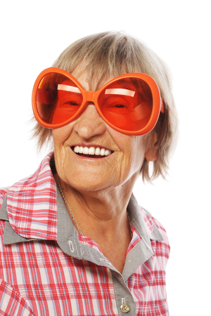 old people: Senior woman wearing big sunglasses doing funky action isolated on white background Stock Photo