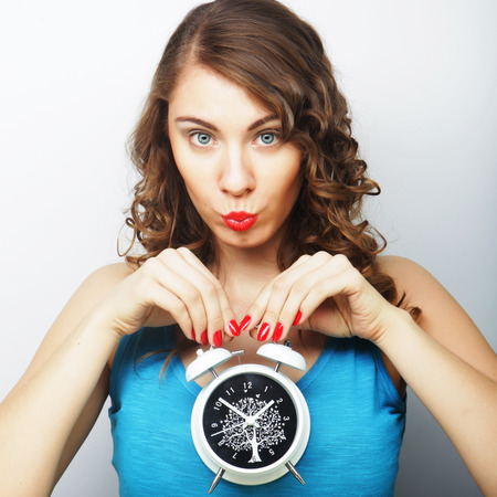 Young happy curly woman with alarmclock photo