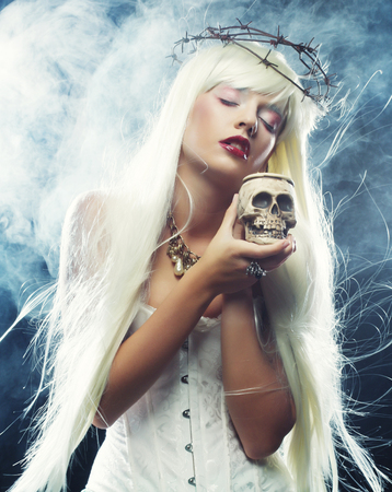 cute angel: Picture a beautiful angelic long hair woman with skull Stock Photo