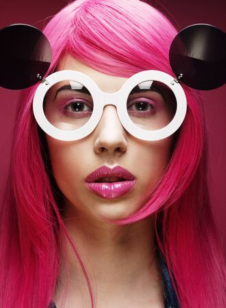 Beautiful fashion model  with pink hair and make-up wearing big sunglasses photo