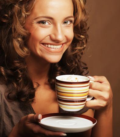 Beautiful young girl drinking tea or coffee photo