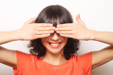 Young woman covering her eyes with her hands.Studio shot.
