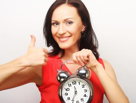 alarmclock: Young happy brunette  woman with alarmclock