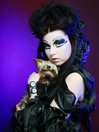 elegant dark queen with little dog photo