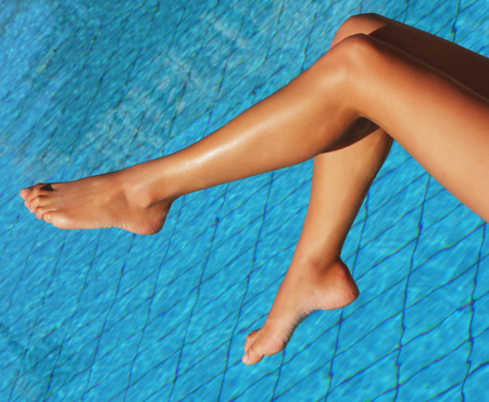 suntanning: Sexy female legs at blue water of swimming pool