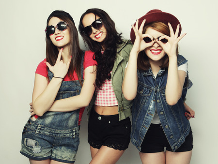 Three stylish sexy hipster girls best friends.Standing together and having fun. Looking at camera. Over gray background. Standard-Bild