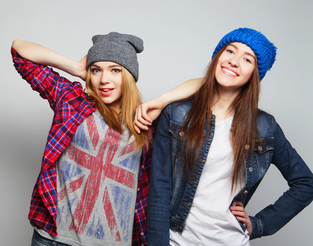 teenage love: Fashion portrait of two stylish sexy hipster girls best friends, wearing cute swag outfits and hats. Over gray backround.