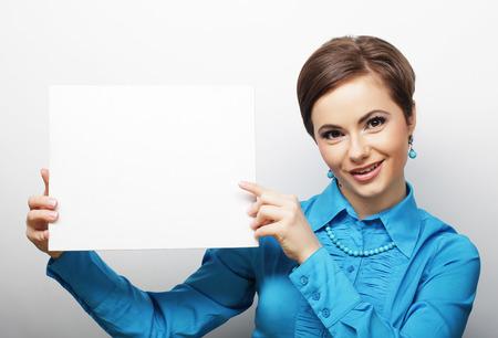 hoja en blanco: casual joven mujer feliz celebración de signo en blanco, tiempo feliz Foto de archivo