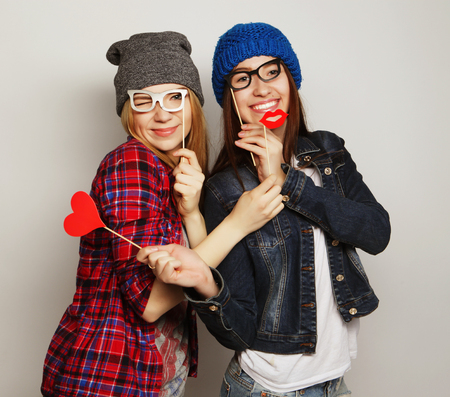two stylish hipster girls best friends ready for party, over gray background Banco de Imagens