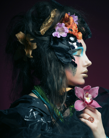 young woman with creative make up holding pink flower