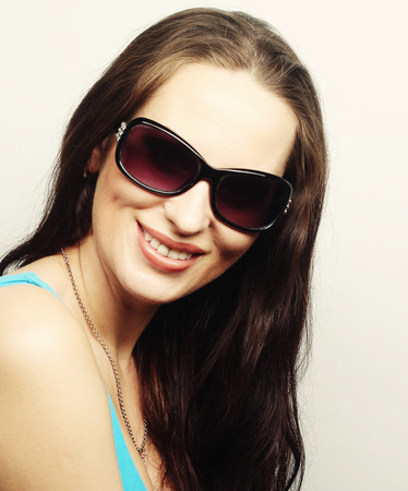 brunette portrait with sunglasses over gray background photo