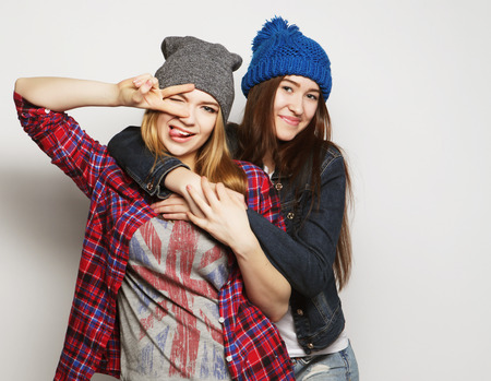 two young girl friends standing together and having fun. Showing signs with hands. Looking at camera