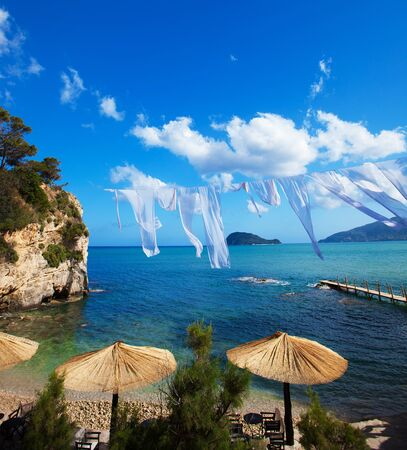 lounges: Row of Straw umbrellas and lounges at  beach Zakynthos, Greece