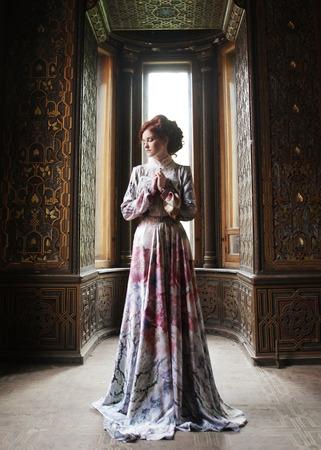 vestidos antiguos: joven y bella mujer en vestido rosa posando en palacio de lujo Foto de archivo